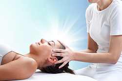 Woman receiving Reiki healing.